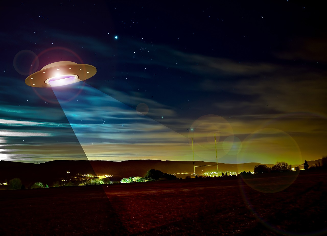 An illustration of a UFO spaceship at night, shining light onto an Earth landscape below
