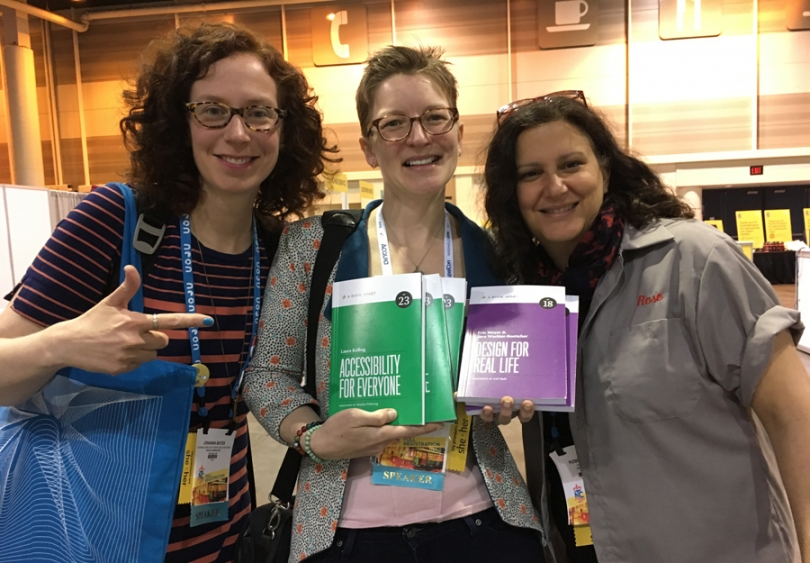 "Johanna Bates, Eileen Webb, and Rose Liebman standing together, smiling, holding books ""Accessibility for Everyone"" and ""Design for Real Life"""